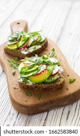 Open sandwiches with fresh vegetables( cucumber, radish, avocado and greens on a wooden cutting board close up. Selective focus. Copy space