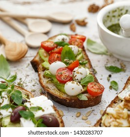 Open sandwiches, in the middle of board an open avocado sandwich made of slice of sourdough bread with the addition of cherry tomatoes, mini mozzarella, fresh basil, olive oil and oregano, close-up