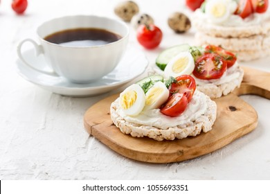 Open sandwiches of rice cakes with cream cheese , vegetables and quail egg, healthy breakfast