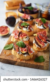 Open sandwiches with ricotta cheese, honey and figs on a white background