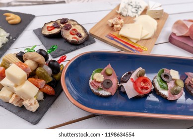 Open sandwiches with sausages, olives, capers, tomatoes and cheese ready to eat at the party. Top view