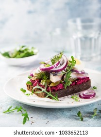 open sanwich with dark rye bread, beet, marinated herring, pickled cucumber and red onion, smorrebrod, selective focus