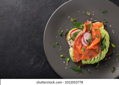 open sanwiches with dark rye bread, avocado, smoked salmon and radish, black background, top view,