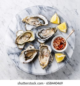 Open shucked Oysters with lemon and spicy sauce on white marble background