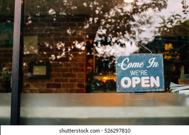 Open sign board close-up through the glass of a window at coffee shop door. Shallow depth of field.