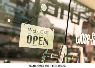 Open sign broad through the glass of window at coffee shop.