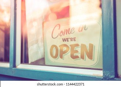 Open sign broad through the glass of door in cafe with colorful bokeh light abstract background. Business service and food concept. Vintage tone filter effect color style.