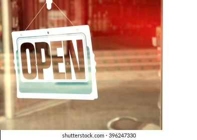 Open sign broad through the glass of door in cafe. Retro color effect.