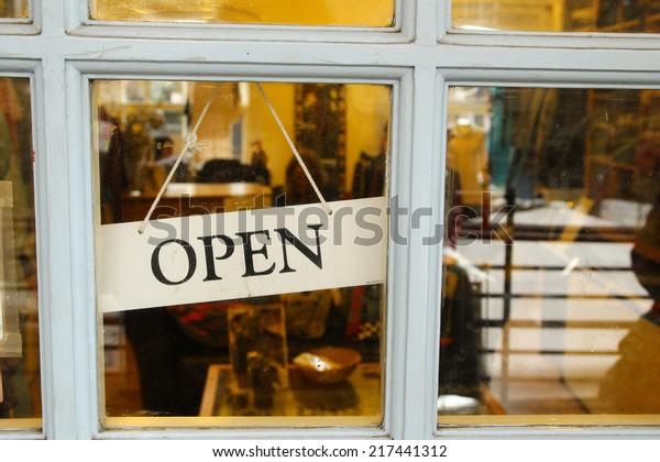 An open sign hanging in a door of a shop