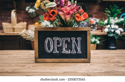 Open sign on wooden table among flowers bouquet