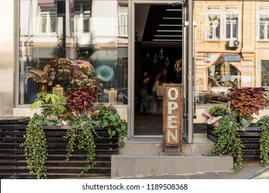open signboard, potted plants and reflecting windows at flower shop