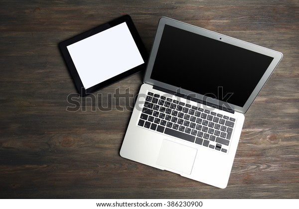 An open silver laptop and modern tablet on the wooden background