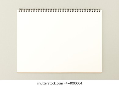 Open sketchbook with blank white page on neutral background - great template for your drawing, hand lettering or design work