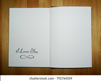 An open sketchbook with `I Love You` and eternity symbol written by pencil on wooden table