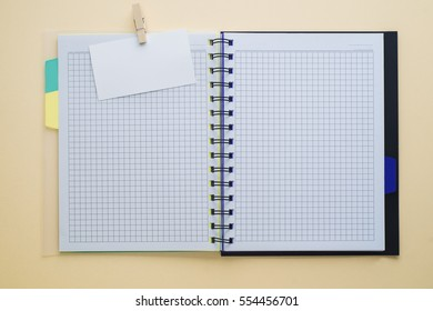 Open sketchbook or scrapbook with blank white business card, mock up template. Empty white notebook on wooden table, flat lay. Top view.