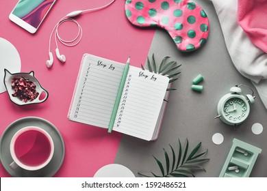 Open sleep log or sleeping diary book. Healthy night sleep creative concept. Sleeping mask, alarm clock, earphones, earplugs, calming tea and pills. Split two tone pink and green paper background.