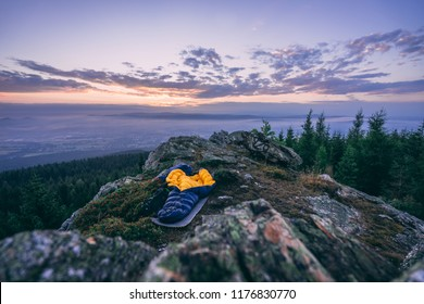 An open sleeping bag laying on the ground on a rock, forest in the background. Sunrise or sunset sky, purple colors and beautiful mountain landscape.