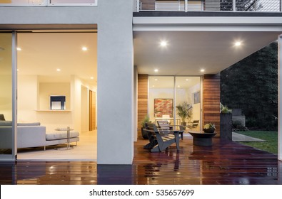 Open sliding door with wooden deck at night with furniture.
