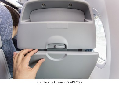 Open the small table behind the airplane seat