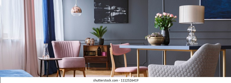Open space living room interior with poster on grey wall with wainscoting, window with drapes and pink armchair