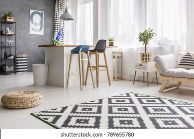Open space living room interior with geometric carpet and dining area with barstools and white bin