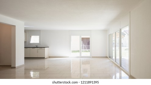 Open space with living room and kitchen. Large bright windows, nobody inside