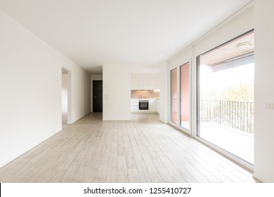 Open space living room with large windows overlooking the nature. Nobody inside