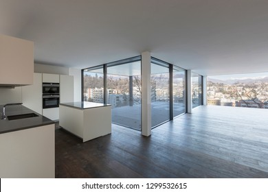 Open space with modern kitchen and large windows overlooking the city and hills