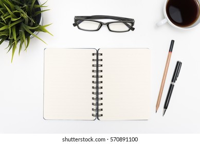 Open spiral blank notebook with pen, pencil, eye glasses, cup of coffee and small flower on white desk table background, flat lay top view