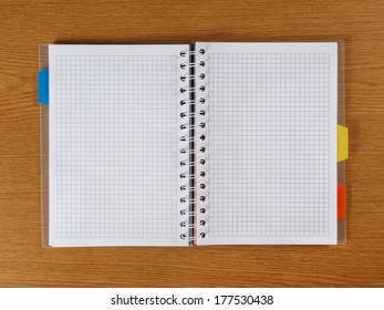 Open spiral notebook lying on a desk