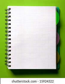 Open spiral notebook on green table