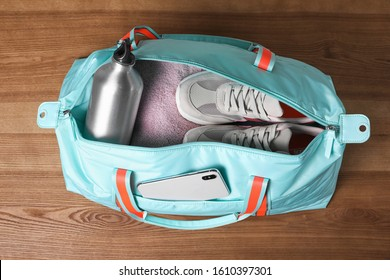 Open sports bag full of gym stuff on wooden background, top view
