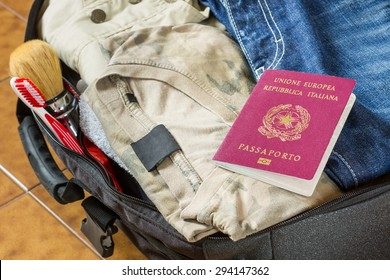 An open suitcase with clothes, personal effects and an italian passport on it