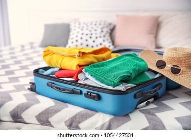 Open suitcase with different personal stuff on bed