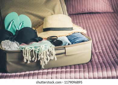 Open suitcase with female clothes for beach vacation on the bed. Packing things.