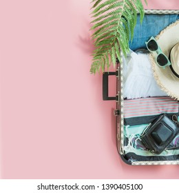 Open suitcase with female clothes, leaf of fern, tropical detox water on pastel pink. Top view with copy space. Summer travel concept.