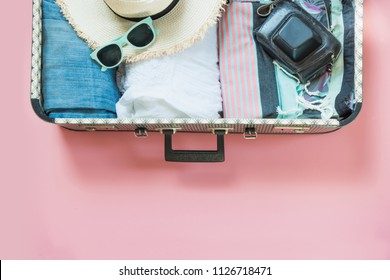 Open suitcase with female clothes for trip on pastel pink background. Top view with copy space. Summer concept travel.