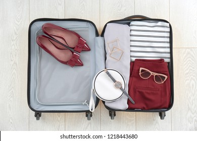 Open suitcase with female clothing, shoes and accessories on wooden background