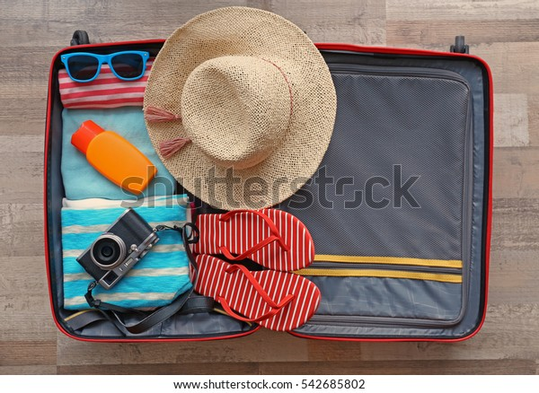 Open suitcase packed for travelling, close up
