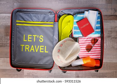 Open suitcase packed for vacation on floor. Text LET'S TRAVEL on background