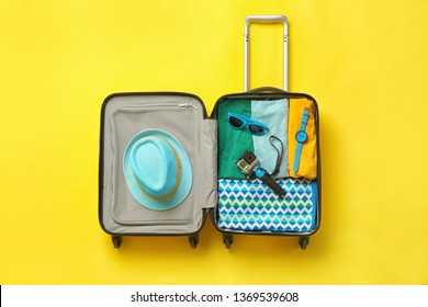Open suitcase with summer clothes and accessories on color background, top view