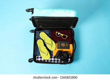 Open suitcase with traveler's belongings on color background, top view