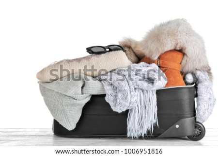 e7f1cee9278 Open suitcase with warm clothes on wooden table against white background.  Winter vacation concept