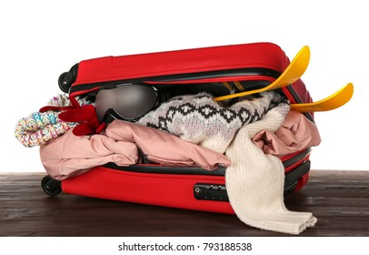 Open suitcase with warm clothes and ski outfit on wooden table against white background. Winter vacation concept