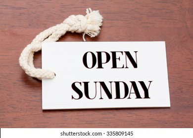 Open sunday words printed on a whitepaper tag or label on wood