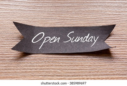 Open Sunday words written on Black papper with wooden background