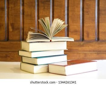 Open textbook on top of books with wood background, an education concept