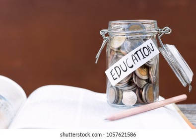 Open textbook, pencil, and coins in a glass bottle on the table. The concept of intelligence comes from education. selective focus.