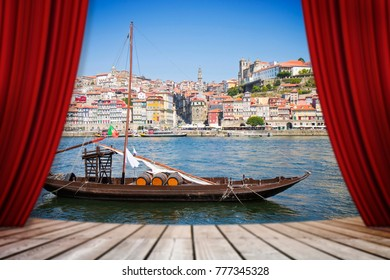 """Open theater red curtains against a typical portuguese wooden boats, called """"barcos rabelos"""", used in the past to transport the famous port wine (Porto-Portugal-Europe)"""