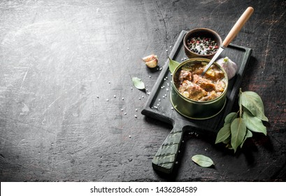 Open a tin of canned meat on a cutting Board with the Bay leaves and the cloves of garlic. On dark rustic background